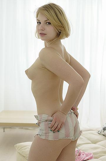 18 virgin sex carolin sits back naked on a cozy sofa 10