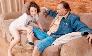 Curious man spies on a hot babe relaxing on a couch
